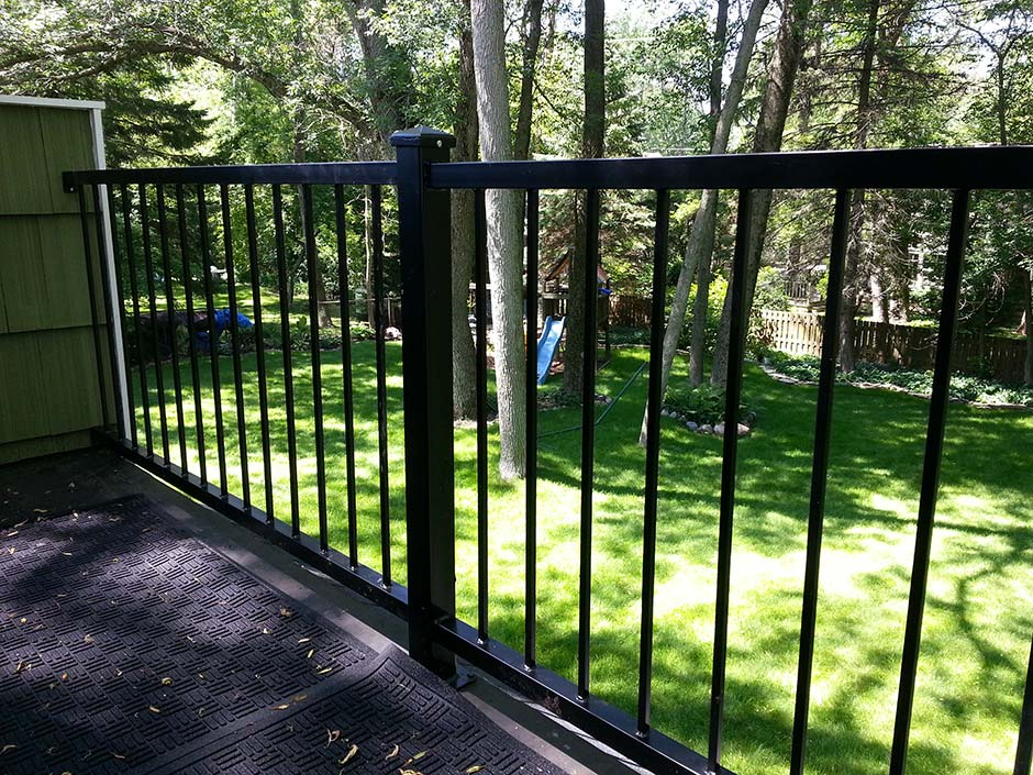 A view between the black railing of a home balcony.