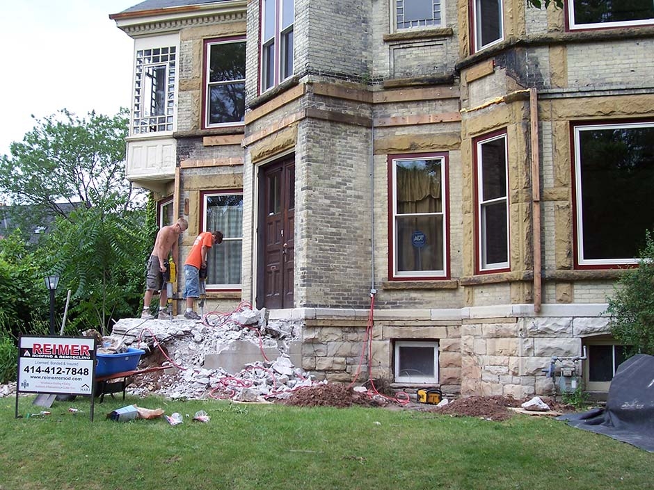 Two men using jack hammers during a exterior home remodel in Waukesha.