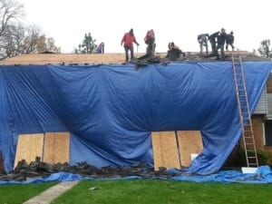 A home covered in a blue tarp while a roofing crew works on putting up a new roof.
