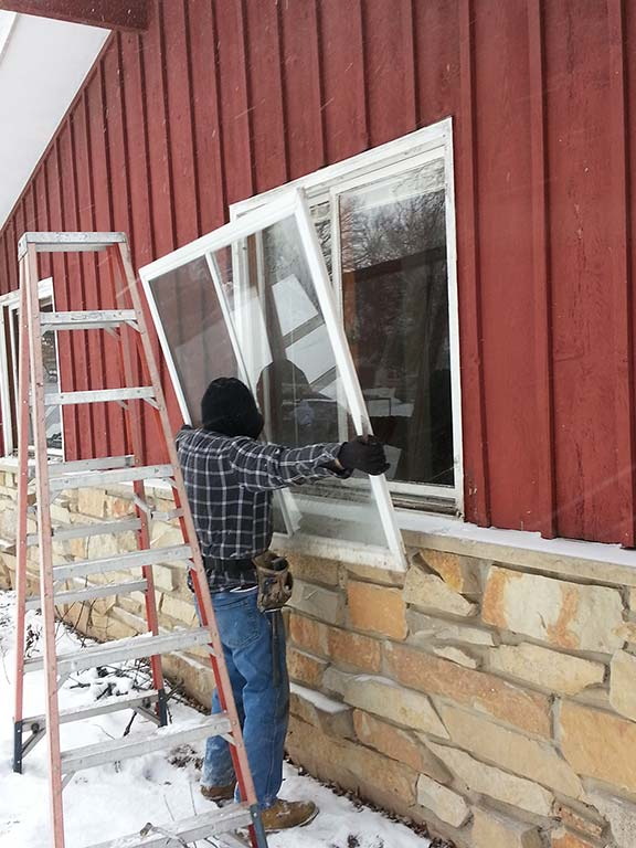 A man outside Lifting up a new window into the frame outside of a house.