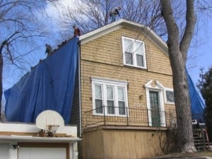 A home with a tarp hanging from the roof down the side as three men work on the roof.