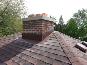 The top of a roof with brand new shingles.