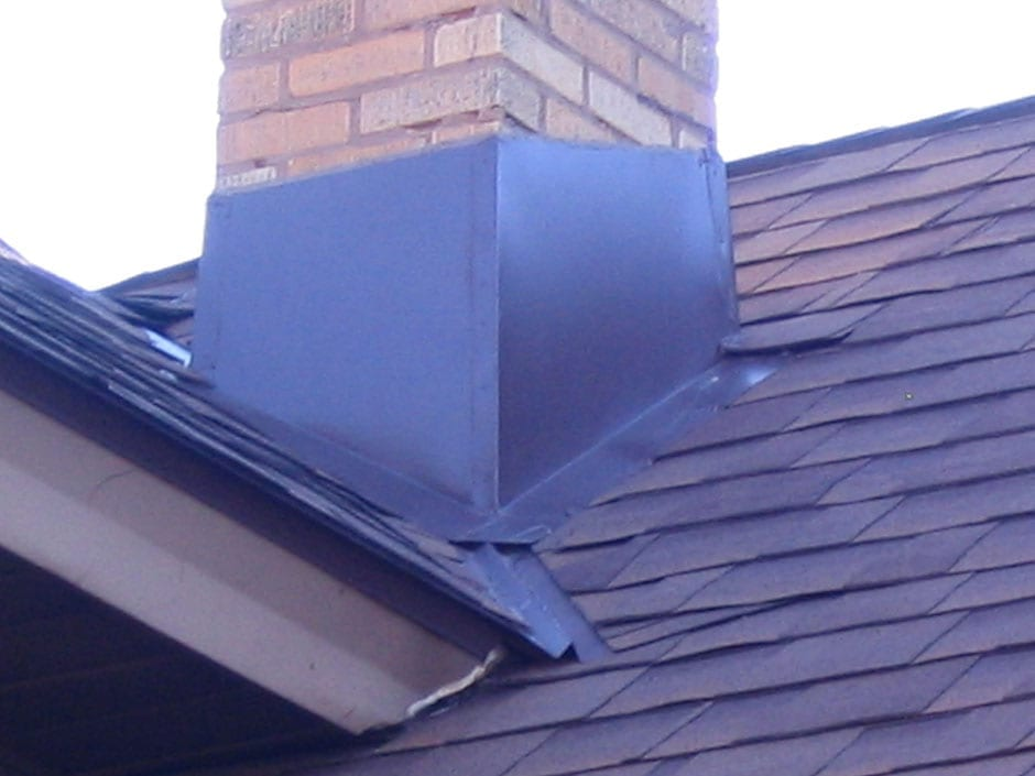 A close up of a chimney repair on top of a roof.