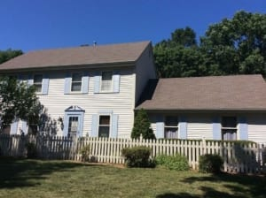A Muskego home with blue shutters, a fence, and a new roof.