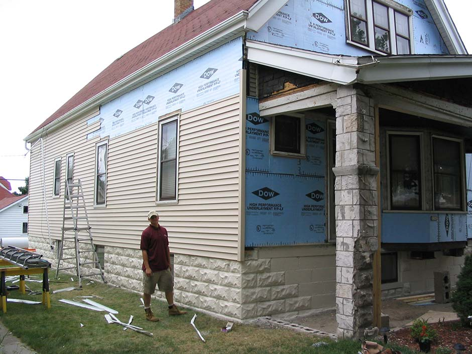 A man standing next to home undergoing a siding replacement in Brookfield.