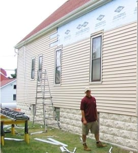 A man walking on the side of a house during a roofing project.