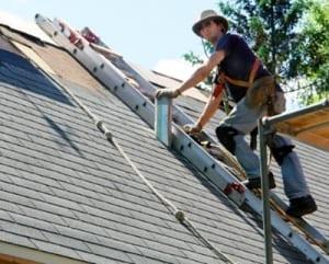 A man on a ladder climbing a roof.