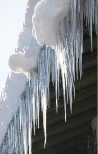 Icicles and snow hanging from a roof.