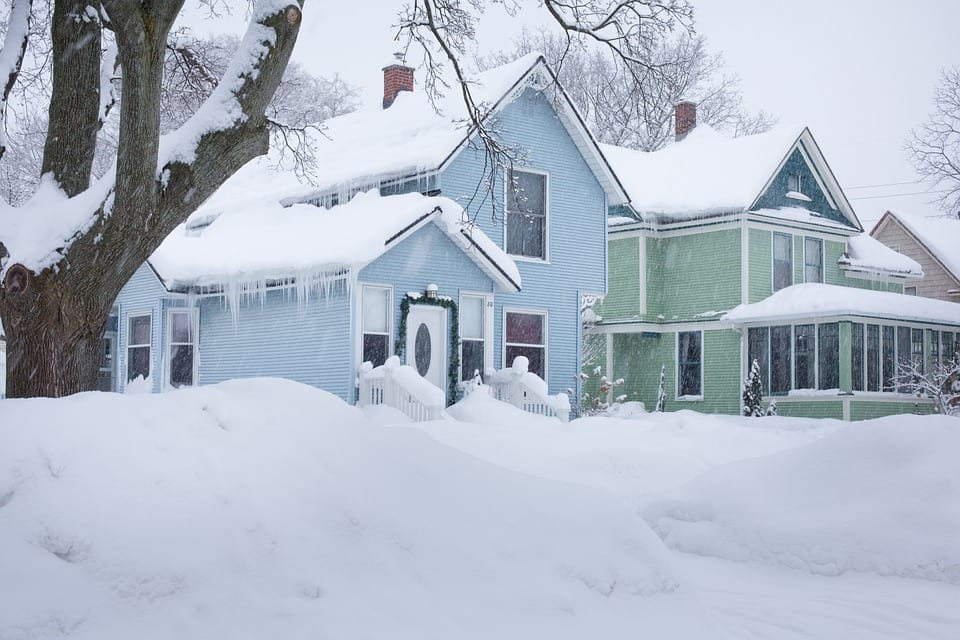 A blue home and a green home side by side covered with snow in the winter.
