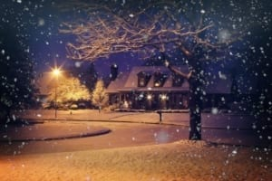 A view of a home in a neighborhood on a snowy night.
