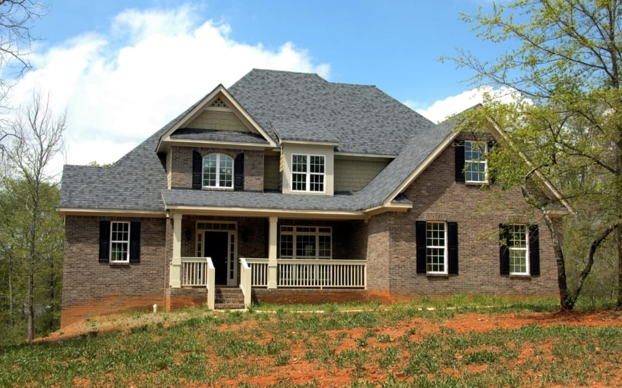 A two-story brick home with a cream colored front porch and black trim around the windows.