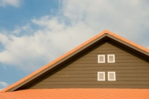 The top peak of a roof on a brown house with orange siding.